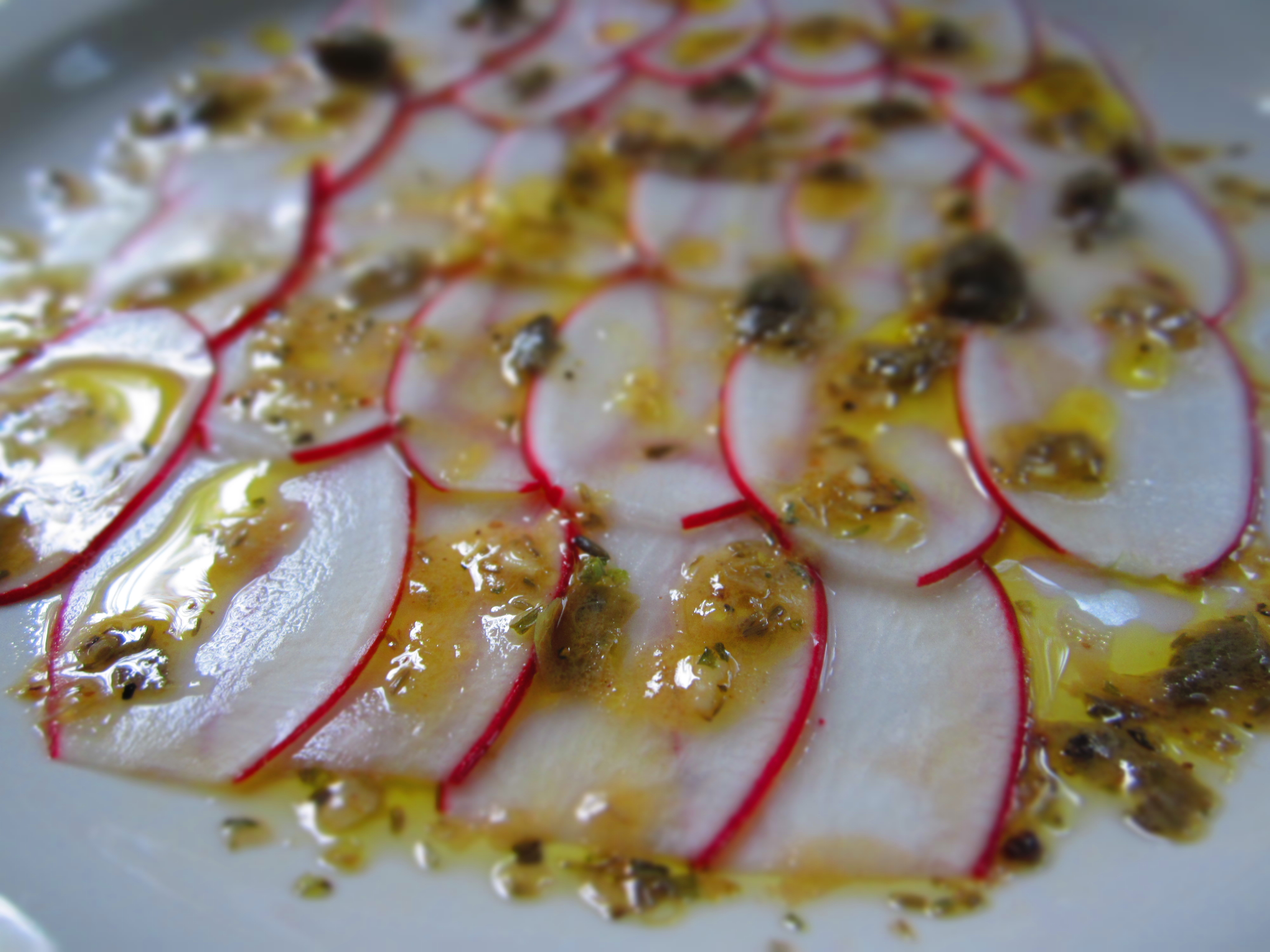 Radish Carpaccio with capers and herbs vinaigrette.