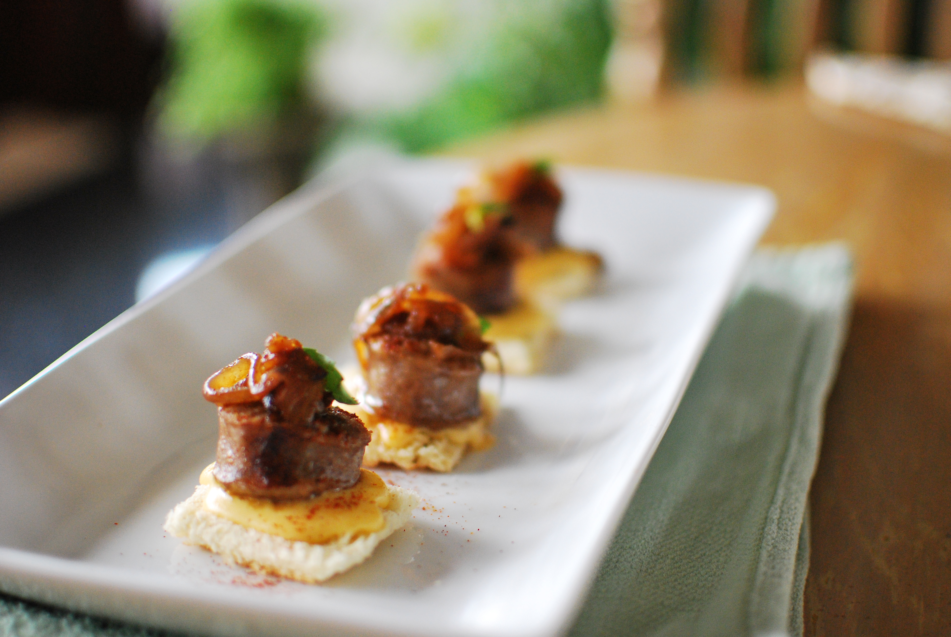 Grilled Bratwurst Appetizer with Dijon-Cheddar Fondue, Caramelized Onions, and Basil